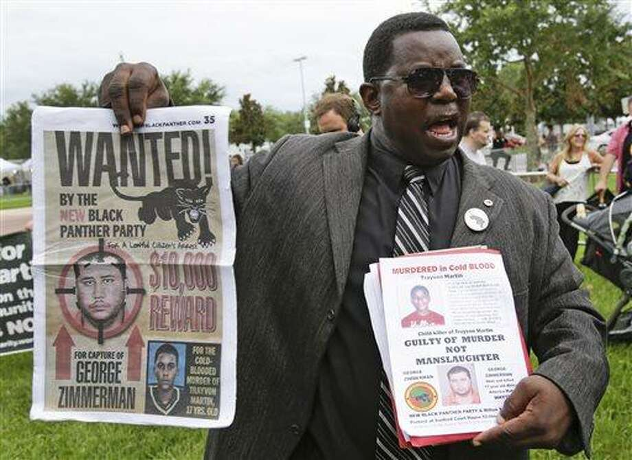James Evan Muhammad, of the New Black Panther Party, demonstrates in front of the Seminole County Courthouse while the jury deliberates in the trial of George Zimmerman, Friday, July 12, 2013, in Sanford, Fla. Zimmerman has been charged in the 2012 shooting death of Trayvon Martin. (AP Photo/John Raoux) Photo: AP / AP