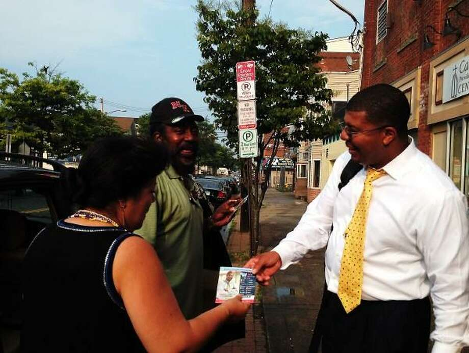 Mayoral candidate Kermit Carolina approaches a couple with his campaign literature during a canvass of Grand Avenue in Fair Haven. June 9, 2013.