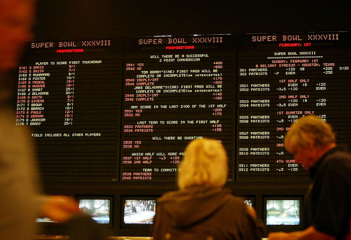 Bettors check out the odds for the Super Bowl Tuesday, Jan. 27, 2004, at the sports book of the Stardust Hotel & Casino in Las Vegas. Super Bowl Sunday is the biggest day for sports wagering in Las Vegas and visitors cram the casinos to bet on and watch the game. (AP Photo/Joe Cavaretta)
