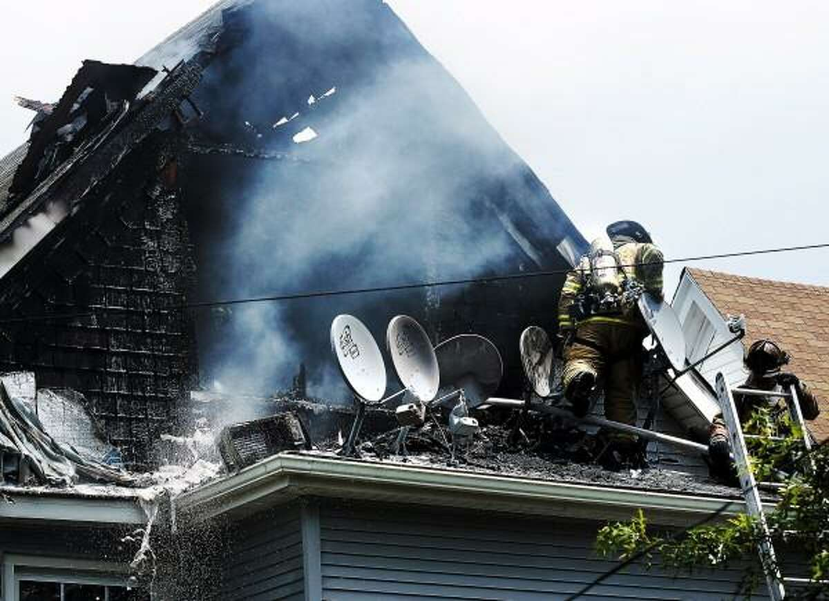 Peter Casolino/New Haven Register Firefighters from several districts in West Haven battle a blaze at 817 Campbell Ave in the early afternoon on Tuesday. pcasolino@newhavenregister.com