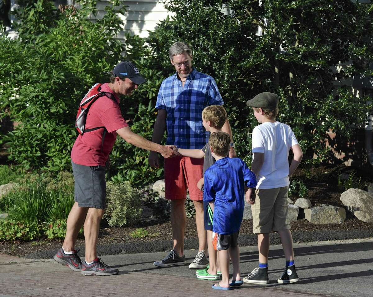 While walking across Connecticut for the second consecutive summer, Sen. Chris Murphy stops to greet Ryan Clancy, of Newtown, and his sons, Finn,Beau and Oliver on Wednesday.