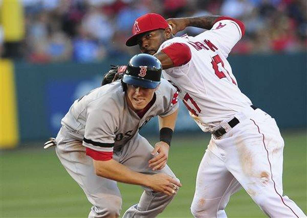 Los Angeles Angels second baseman Howie Kendrick, right, throws to first, completing the double play, after tagging out Boston Red Sox's Brock Holt, left, in the fifth inning of a baseball game, Sunday, July 7, 2013, in Anaheim, Calif. (AP Photo/Gus Ruelas)