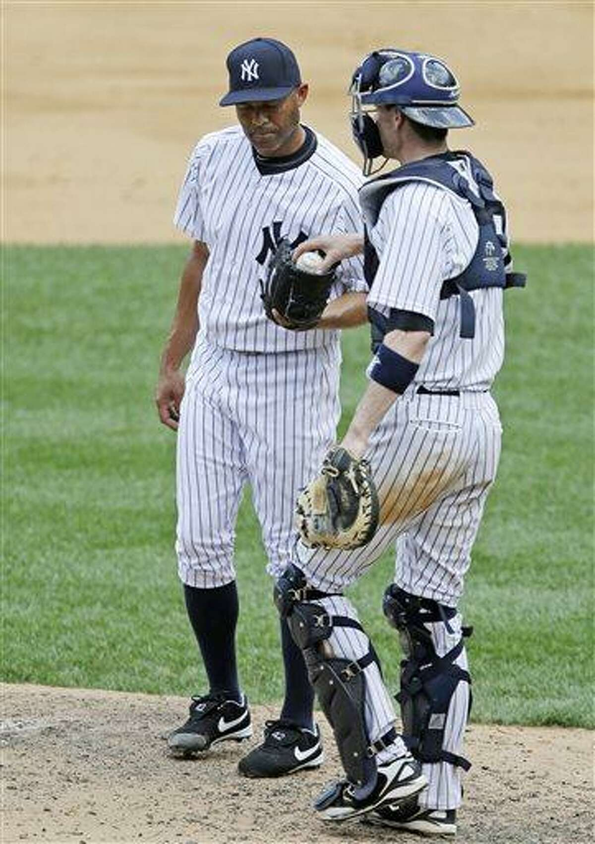 New York Yankees catcher Chris Stewart, right, hands a ball to New York Yankees relief pitcher Mariano Rivera after Rivera gave up a two-run home run to Baltimore Orioles Adam Jones, and then allowed a ground rule double to Matt Weiters in the Yankees 2-1 loss to the Orioles in a baseball game, Sunday, July 7, 2013, in New York. (AP Photo/Kathy Willens)