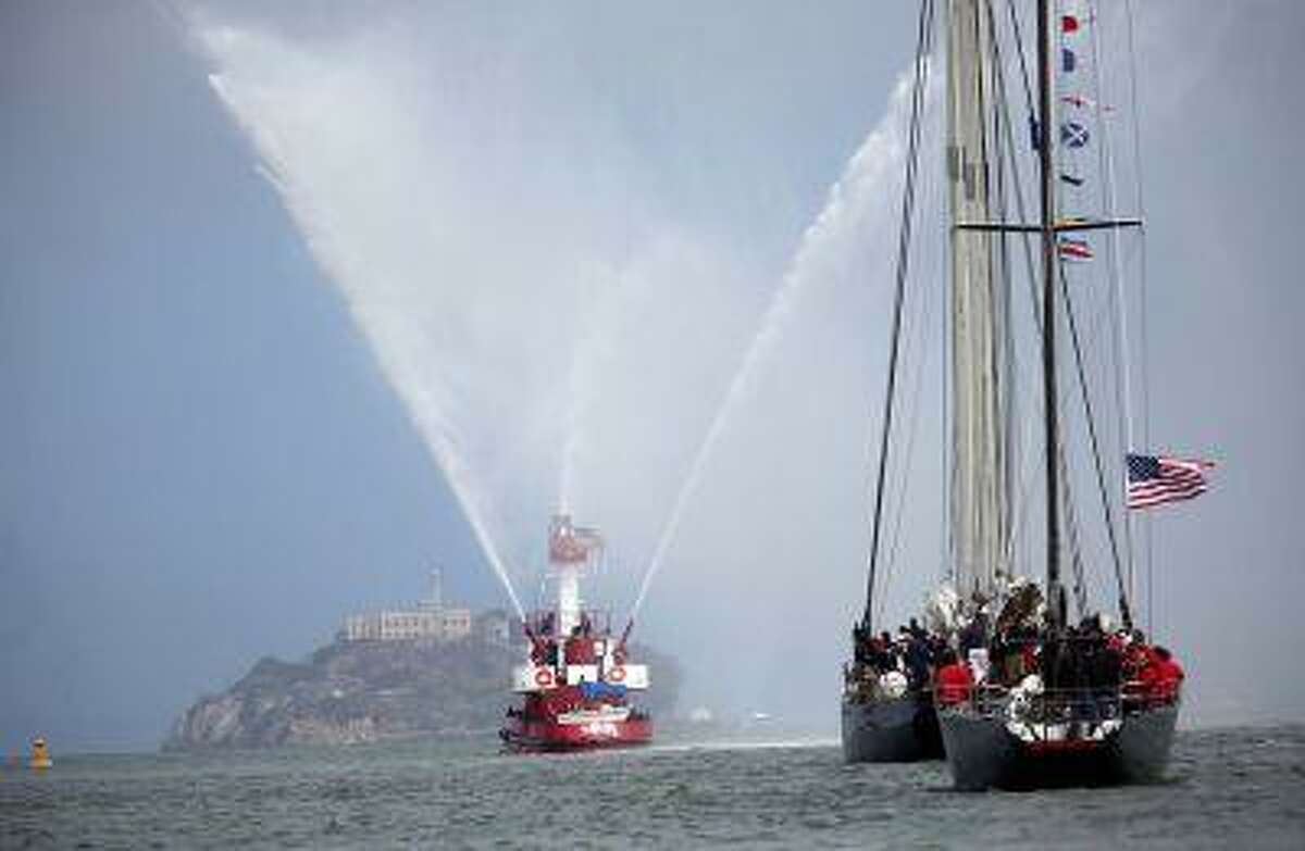 A San Francisco Fire Department boat leads the way, followed by a schooner and an America's Cup boat from 1976, as they past Alcatraz Island during the America's Cup Parade of Boats in San Francisco, Calif., on Friday, July 5, 2013.