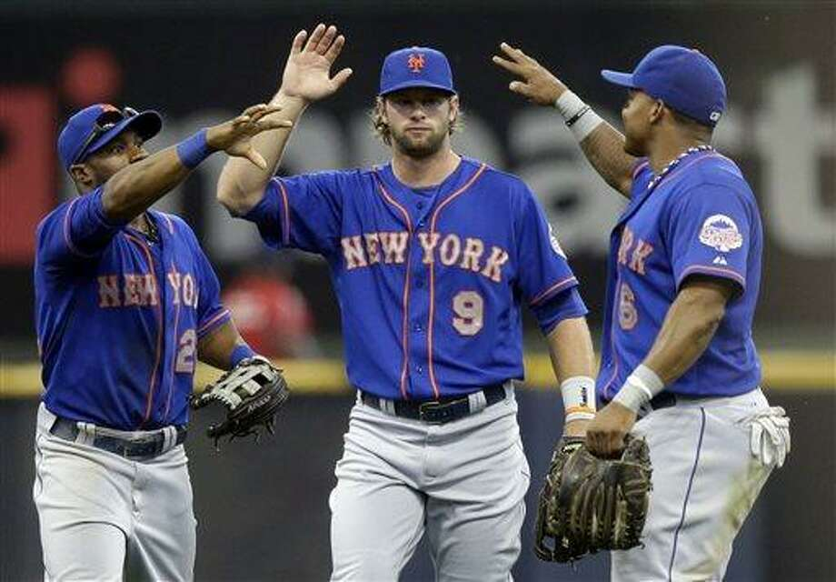 From left to right, New York Mets' Eric Young Jr., Kirk Nieuwenhuis and Marlon Byrd celebrate after a baseball game against the Milwaukee Brewers, Sunday, July 7, 2013, in Milwaukee. The Mets won 2-1. (AP Photo/Morry Gash) Photo: AP / AP