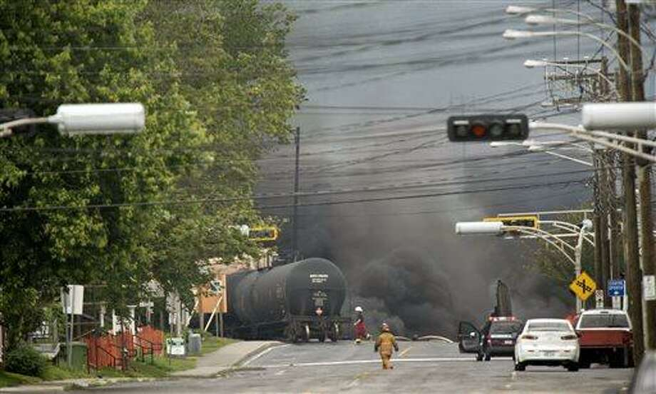 Smoke rises from railway cars that were carrying crude oil after derailing in downtown Lac Megantic, Quebec, Canada, Saturday, July 6, 2013. The derailment sparked several explosions and forced the evacuation of up to 1,000 people. (AP Photo/The Canadian Press, Paul Chiasson) Photo: AP / The Canadian Press