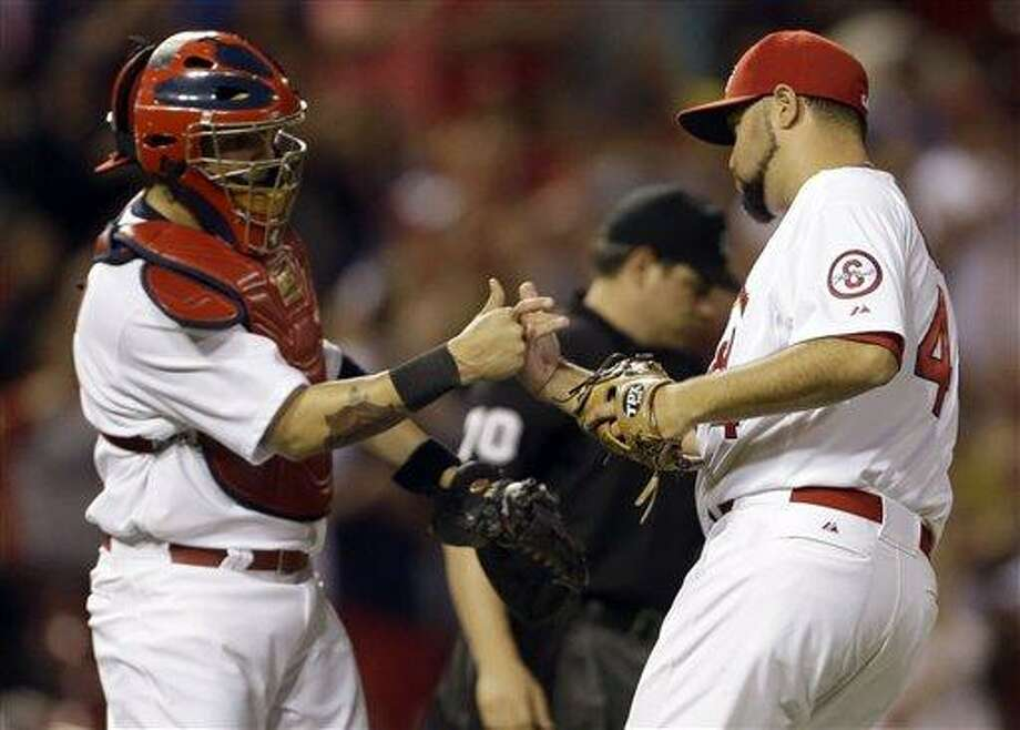 St. Louis Cardinals catcher Yadier Molina, left, and relief pitcher Edward Mujica celebrate following the Cardinals' 5-2 victory over the Chicago Cubs in a baseball game on Monday, June 17, 2013, in St. Louis. (AP Photo/Jeff Roberson) Photo: AP / AP