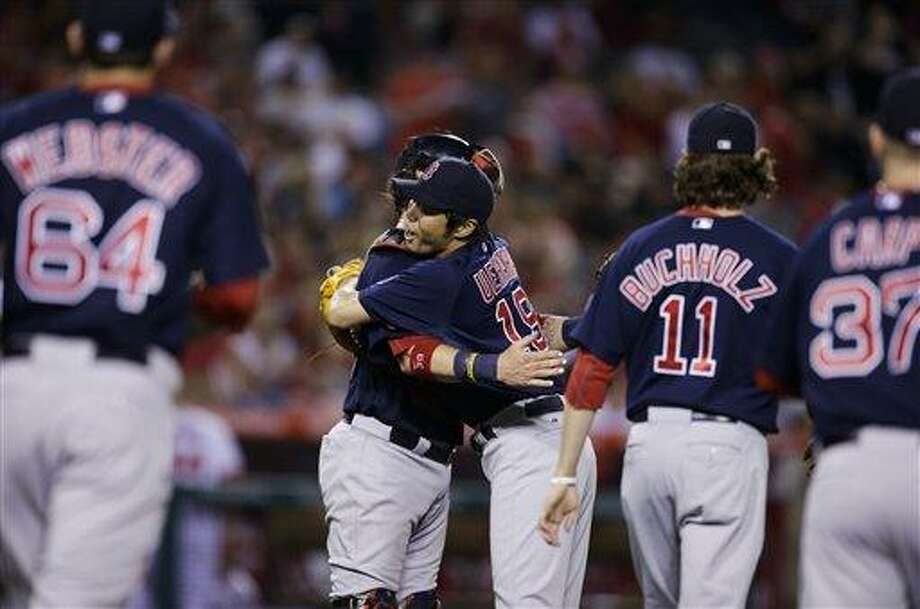 Boston Red Sox relief pitcher Koji Uehara, center left, of Japan, and catcher Jarrod Saltalamacchia celebrate their team's 6-2 win against the Los Angeles Angels after a baseball game in Anaheim, Calif., Friday, July 5, 2013. (AP Photo/Jae C. Hong) Photo: AP / AP