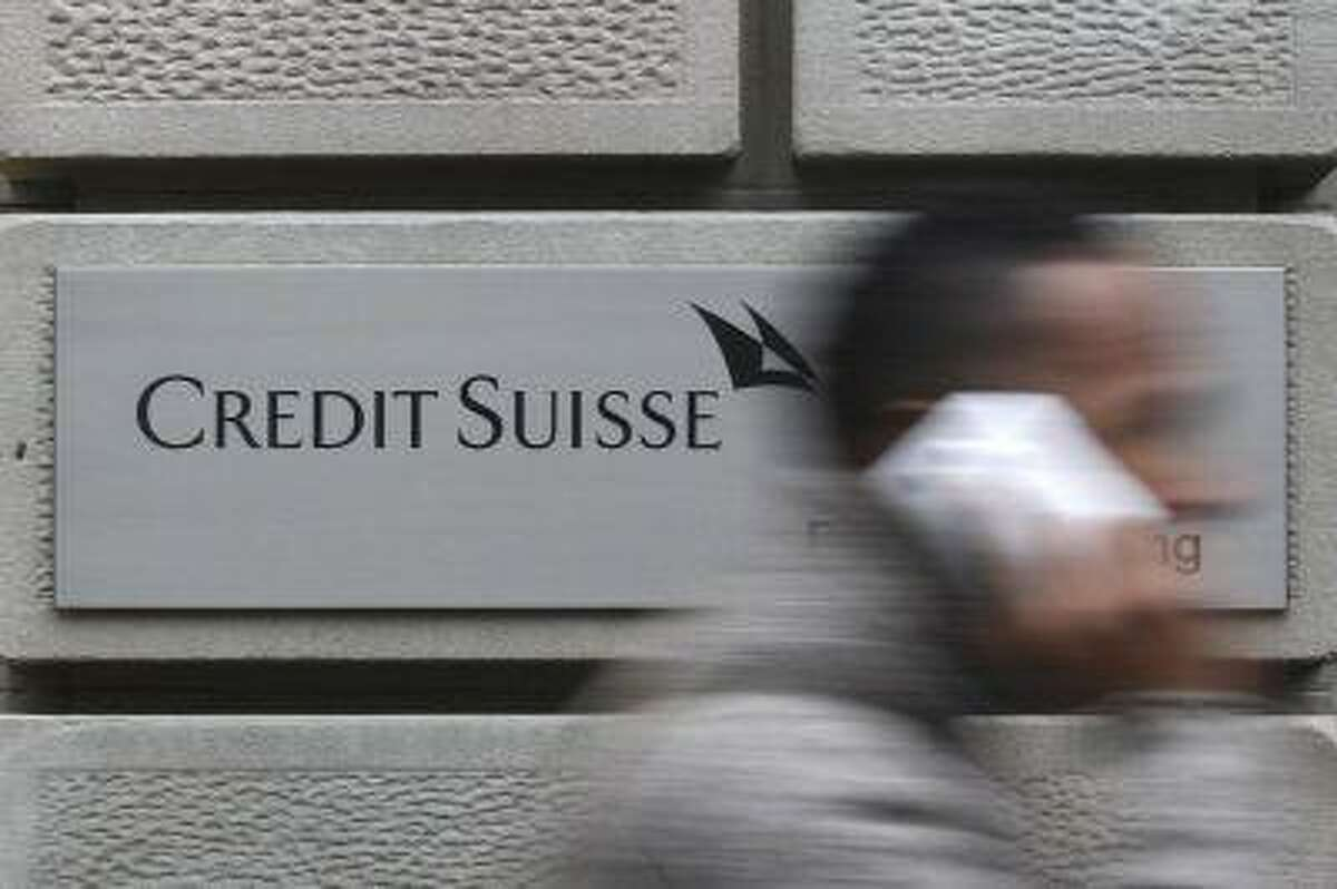 A man uses his cell phone as he walks past a branch of Swiss bank Credit Suisse in Zurich. (Reuters/Christian Hartmann)