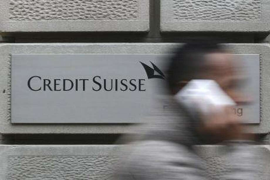 A man uses his cell phone as he walks past a branch of Swiss bank Credit Suisse in Zurich. (Reuters/Christian Hartmann) / X90079