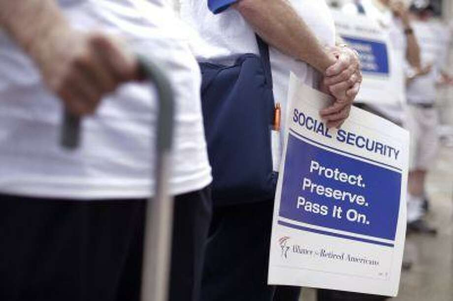 """Demonstrators form a symbolic chain to protest agents a proposed change in the formula for determining annual Social Security benefits known as """"chained CPI,"""" Tuesday, July 2, 2013, in Philadelphia. (AP Photo/Matt Rourke) Photo: AP / AP"""