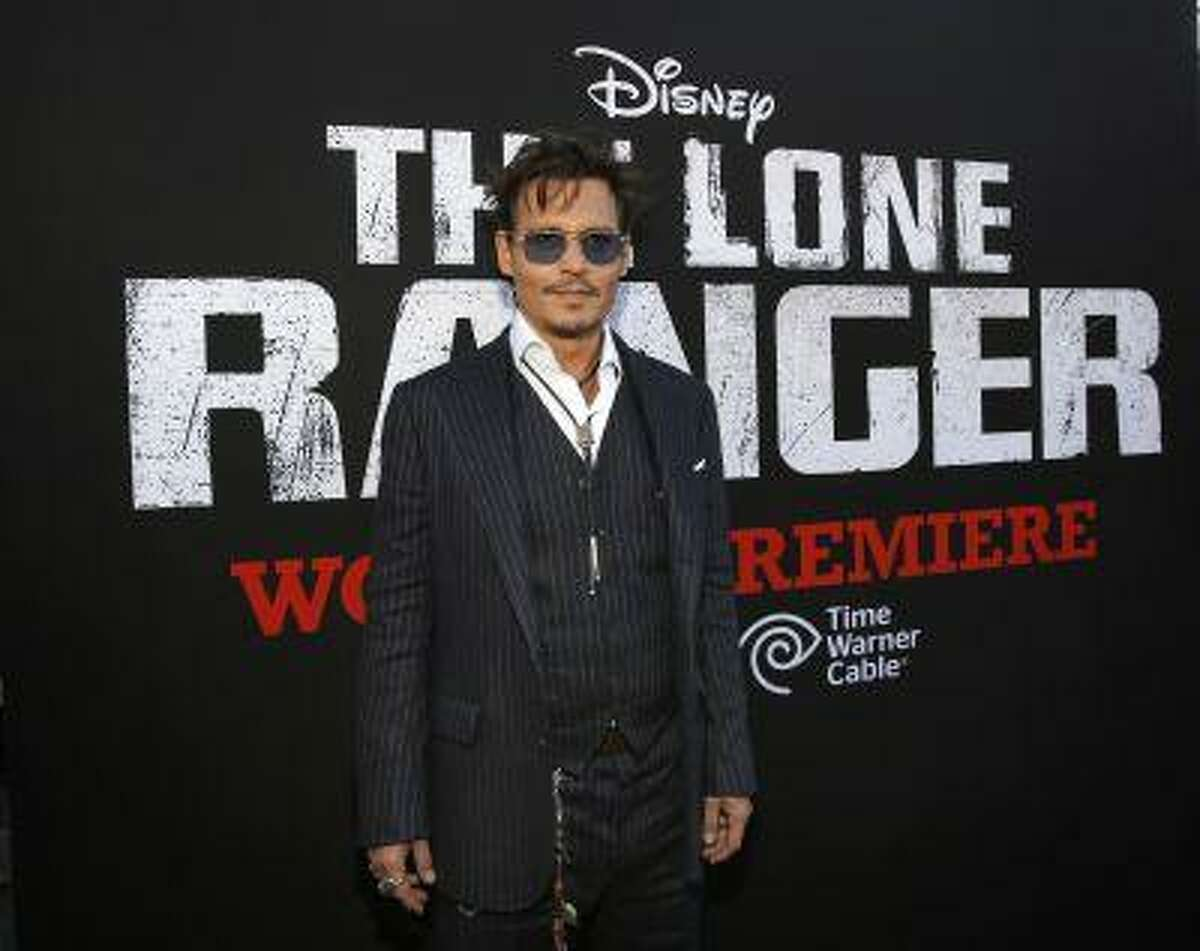 """Cast member Johnny Depp poses at the world premiere of """"The Lone Ranger"""" at Disney California Adventure Park in Anaheim, California in this June 22, 2013, file photo. """"The Lone Ranger,"""" Walt Disney Co's big-budget western starring Depp, performed below expectations on Wednesday night, raising the possibility that the movie could saddle the media giant with a loss on the film. REUTERS/Mario Anzuoni/Files"""