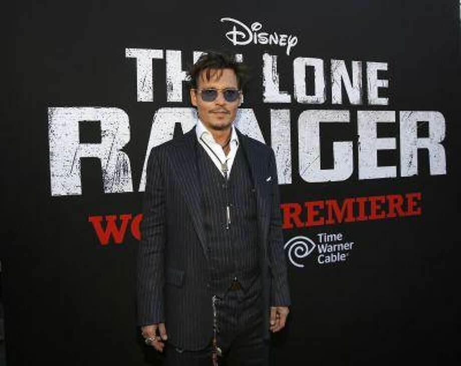 """Cast member Johnny Depp poses at the world premiere of """"The Lone Ranger"""" at Disney California Adventure Park in Anaheim, California in this June 22, 2013, file photo. """"The Lone Ranger,"""" Walt Disney Co's big-budget western starring Depp, performed below expectations on Wednesday night, raising the possibility that the movie could saddle the media giant with a loss on the film. REUTERS/Mario Anzuoni/Files Photo: REUTERS / X90045"""