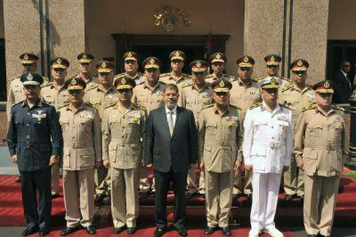 Egypt's President Mohamed Mursi, center, poses for photos between Defence Minister Abdel Fattah al-Sisi and General Sedky Sobhi, chief of staff to Egypt's Supreme Council of the Armed Forces, and other military generals and members of SCAF during the anniversary of Egypt's October 6, 1973 surprise attack, in Cairo in this October 4, 2012 file picture.