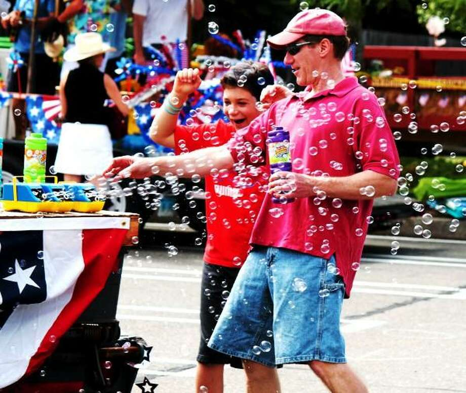 Left, Dan Radka and right, David Radka play with a bubble machine before Madison's Fourth of July parade on 07/04/2013.  Nicole Dellolio/For the Register