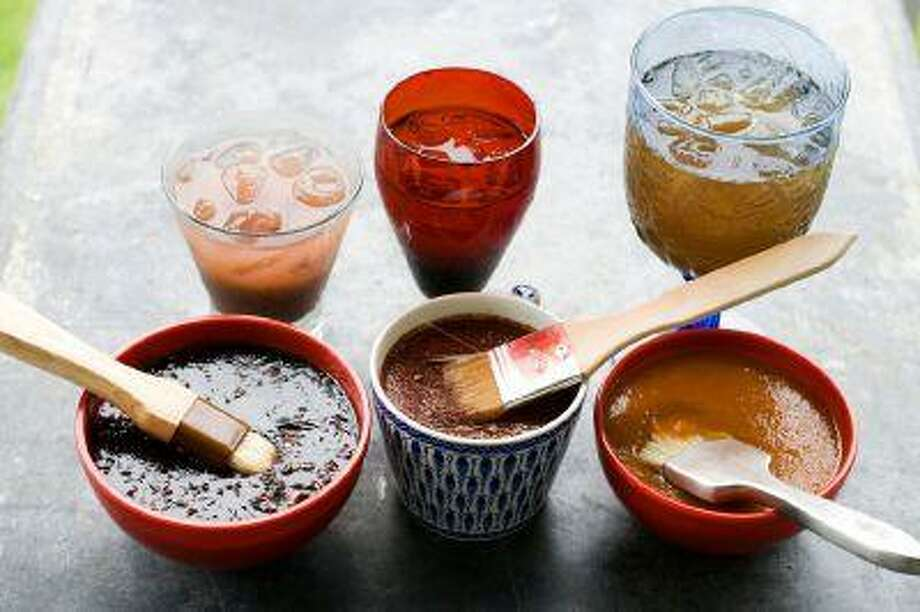 In this image taken on June 10, 2013, from left, balsamic strawberry jalapeno barbecue sauce, recado rojo, and tangy apricot barbecue sauce, are shown with cocktails in Concord, N.H. (AP Photo/Matthew Mead) Photo: AP / FR170582