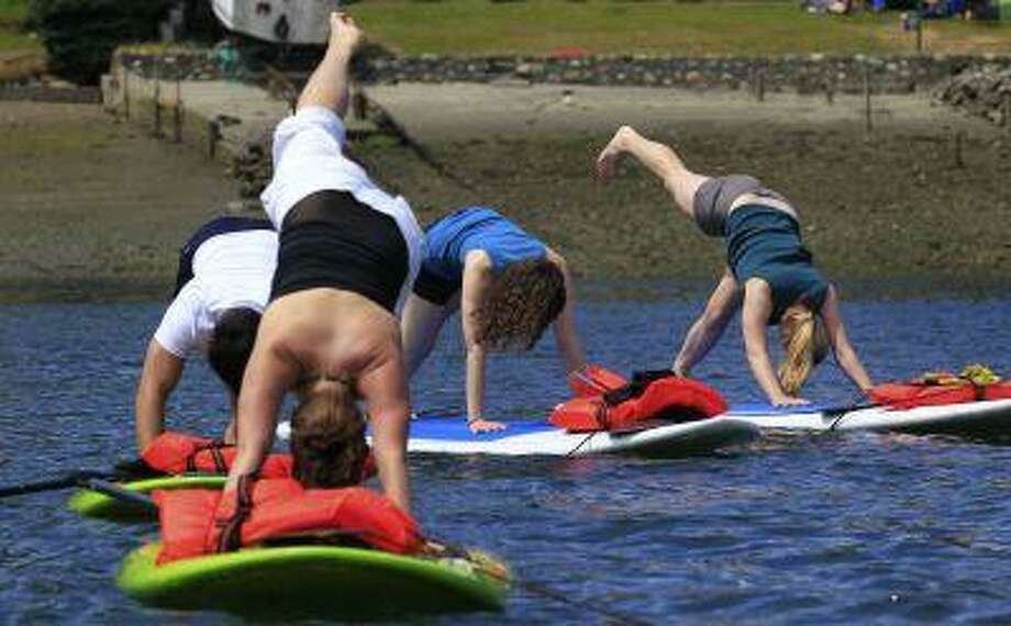 Participants balance during a paddleboard yoga class in Shilshole Bay in Seattle. Paddleboard yoga classes on the cool waters of the Puget Sound, a new way to find your inner chakra, is a trend that's spread from the warmer climates of Florida, California, and Hawaii. (AP Photo/Elaine Thompson) Photo: ASSOCIATED PRESS / AP2011