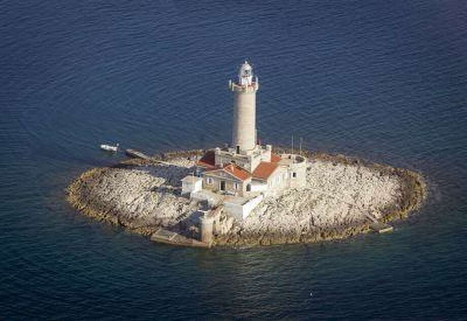 In this photo taken June 17, 2013, a lighthouse Porer in northern Adriatic is photographed from the air. The lighthouse is used for tourist accommodation. On Monday July 1, 2013, Croatia will become the 28th EU member, the bloc's first addition since Bulgaria and Romania joined in 2007. Croatia's membership marks a historic turning point for the small country, which went through carnage after declaring independence from the former Yugoslavia in 1991. (AP Photo/Darko Bandic) Photo: ASSOCIATED PRESS / AP2013