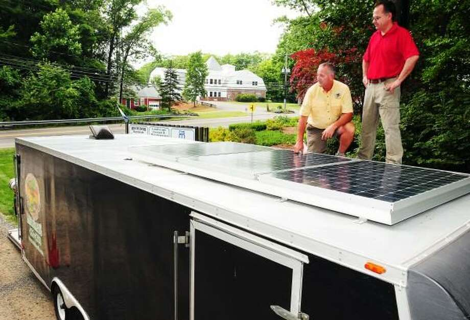 Bob Blundon, owner  of Madison Earth Care Landscaping, left, and Chris Lend, owner of Aegis Solar Energy of Branford,  stand atop a Madison Earth Care Landscaping mowing trailer in Madison Thursday June 27, 2013. Inside the mowing trailer is a 2000 Watt inverter with a solar charge controller designed by Aegis Solar Energy. The solar energy charging system, with 327 watt Sun Power solar panels on the roof of the trailer costs approximately $10,000 dollars with the landscaping equipment and has a 4-month labor and maintenance cost pay back for Blundon. Peter Hvizdak/Register Photo: New Haven Register / ©Peter Hvizdak /  New Haven Register