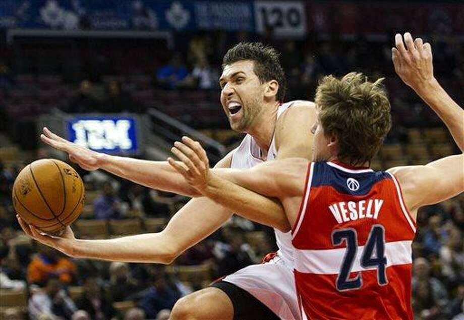 FILE - In this Oct. 17, 2012 file photo, Toronto Raptors forward Andrea Bargnani, left, drives past Washington Wizards forward Jan Vesely during the first half of their preseason NBA basketball game in Toronto. The Knicks and Raptors are discussing a trade to bring former No. 1 pick Bargnani to New York. The Knicks' push to land the forward from Italy was put on hold Sunday, June 30, 2013,  when a deal was not completed, but a person with knowledge of the discussions says the talks will continue. (AP Photo/The Canadian Press, Nathan Denette, File) Photo: AP / The Canadian Press