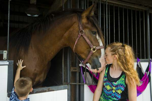 Hannah Sabat of Coleman, 13, right, kisses her grandmother's horse, Dusty, on his nose while Peyton Sabat, 4, left, pets Dusty on Sunday, August 13, 2017 at the Midland County Fairgrounds.