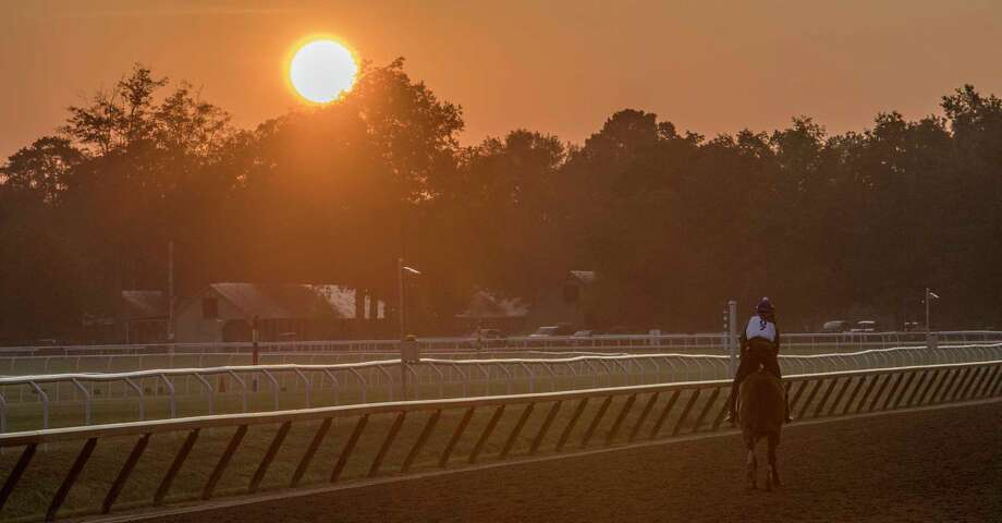 The sun rises as an exercise rider guides his charge around the Oklahoma Training Center early Wednesday Aug. 16, 2017 in Saratoga Springs, N.Y.  (Skip Dickstein/Times Union) Photo: SKIP DICKSTEIN