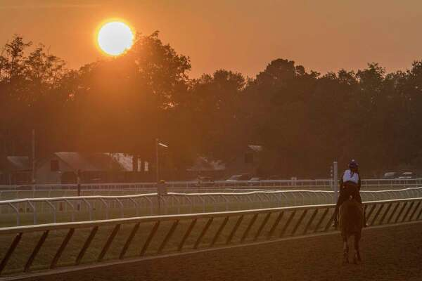The sun rises as an exercise rider guides his charge around the Oklahoma Training Center early Wednesday Aug. 16, 2017 in Saratoga Springs, N.Y.  (Skip Dickstein/Times Union)