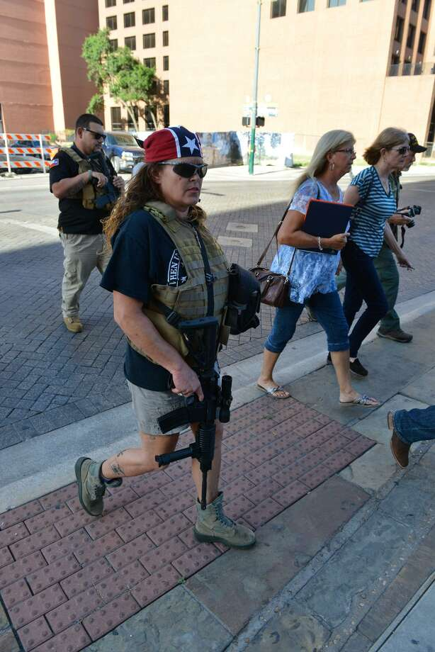 "Erika Wright of the ""This Is Texas Freedom Force"" crosses the street before a San Antonio City Council meeting to listen to residents regarding moving a Confederate statue out of Travis Park. Photo: Robin Jerstad /San Antonio Express News"