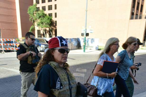"Erika Wright of the ""This Is Texas Freedom Force"" crosses the street before a San Antonio City Council meeting to listen to residents regarding moving a Confederate statue out of Travis Park."