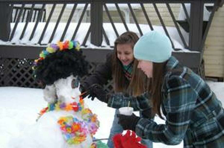 Dispatch Staff Photo by MATT POWERS Debora Soerro and Larissa Mitchell add the finishing touches on the face of their snowman.