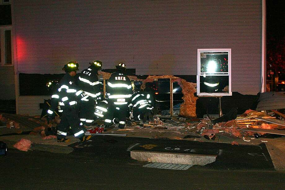 Firefighters work to free a man who was trapped under an SUV as he was sleeping in his bedroom. (William Kaempffer/New Haven Register)