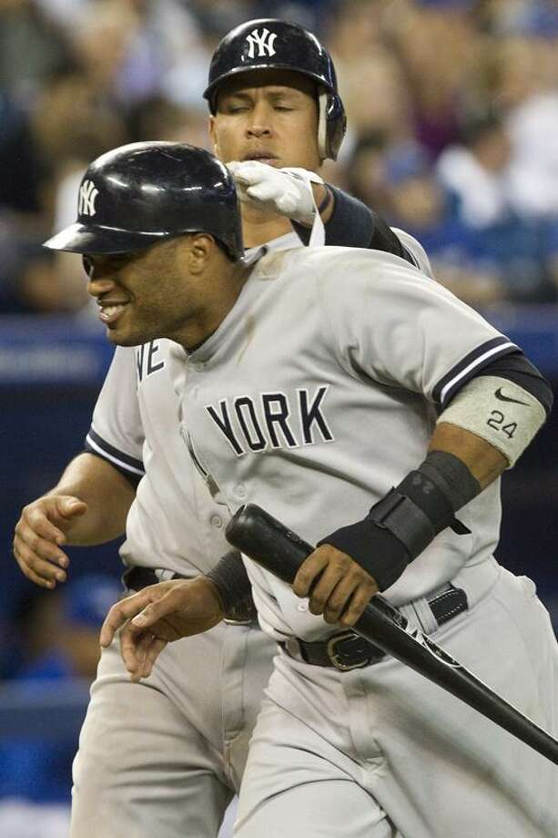 New York Yankees Alex Rodriguez (left) pats Robinson Cano on the back after the pair scored on a single by Curtis Granderson against Toronto Blue Jays during ninth inning of a baseball game in Toronto on Sunday, Sept. 30 , 2012. (AP Photo/The Canadian Press, Chris Young) Photo: AP / CP