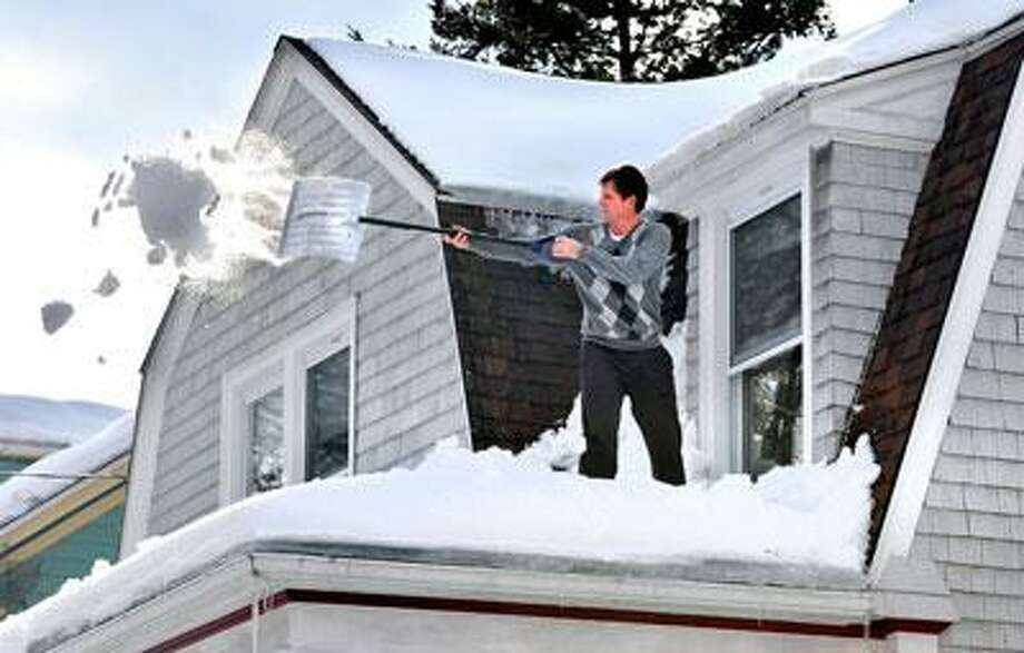 Mike Emmerth clears snow from the roof of his home on West Rock Avenue. (Peter Casolino/Register)