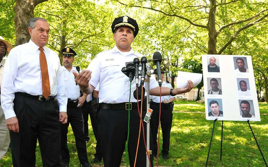 "New Haven Police Chief Frank Limon announces stepped up efforts to bring criminals to justice and names the city's ""Top 10"" most wanted list fugitives during a press conference Tuesday at Kensington Park on Kensington Street as Mayor John DeStefano Jr. looks on. To Limon's left are mugshots of six of the 10 men. The other four fugitives have no prior arrests and therefore no pictures, (Peter Casolino/Register)  05/31/11 Cas110531"