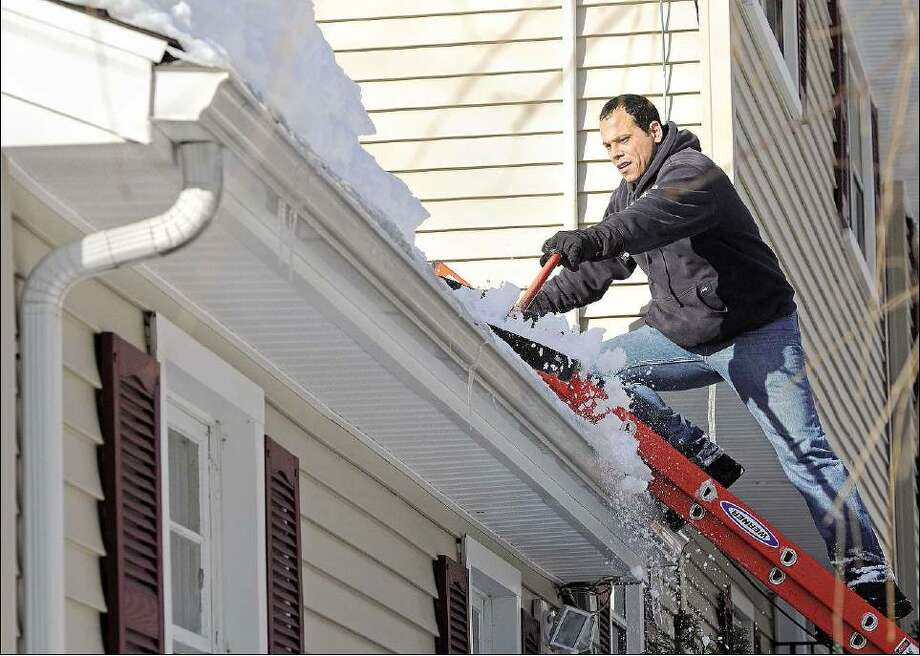Brad Horrigan/Register Lou Santora helps shovel snow off the roof of a friend's garage on Shepard Avenue in Hamden Monday.