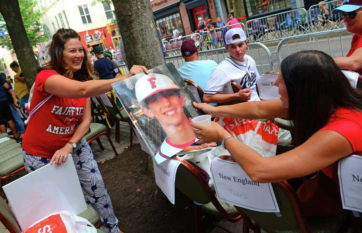 Louise Vivona, right, receives a poster photo of her son Matt from a fellow parent before the start of the 13th annual Grand Slam Parade on Wednesday in downtown Williamsport, Pa.