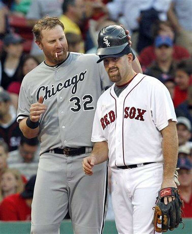 Chicago White Sox's Adam Dunn, left, playfully puts his batting helmet on Boston Red Sox third baseman Kevin Youkilis as he stands on third during a short break in action in the second inning of Tuesday's game. (AP photo) Photo: AP / AP