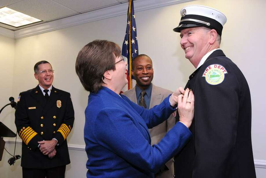 Dennis Harrison gets a new badge pinned on by his wife, Judy, moments after being sworn in as a Hamden fire marshal. Behind them are Hamden Fire Chief David Berardesca and Hamden Mayor Scott Jackson.  Peter Casolino/Register