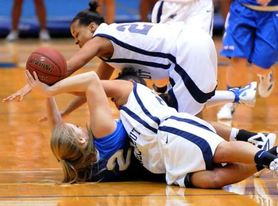Mara Lavitt/Register Assumption's Jamie Insel, bottom, tries to keep the ball away from Southern Connecticut State's  Mariah Hankton, top, and Camille Fantini in Tuesday's game.