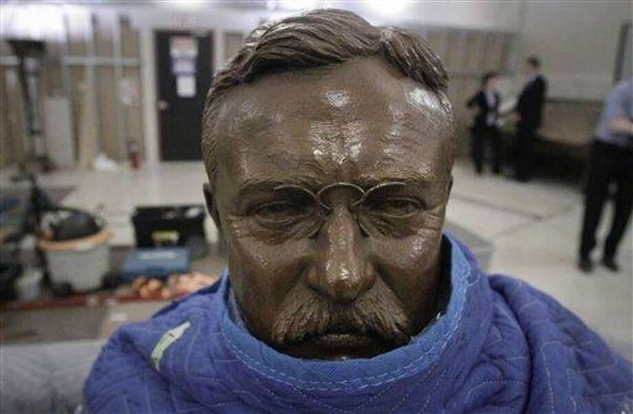 In this Thursday photo, a sculpture of Theodore Roosevelt remains partially wrapped before it is permanently installed on a bench at the American Museum of Natural History in New York. The AMNH is reopening the two-story Theodore Roosevelt Memorial after a three-year, $42.1 million restoration project. (AP Photo/Bebeto Matthews) Photo: AP / AP
