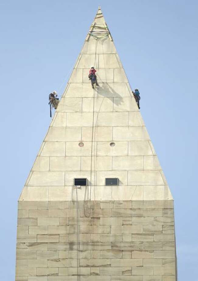 Engineers, from left, Dan Gach, Emma Cardini and Katie Francis, harnessed to ropes, inspect the exterior of the Washington Monument for damage caused by last month's earthquake Wednesday in Washington. Associated Press
