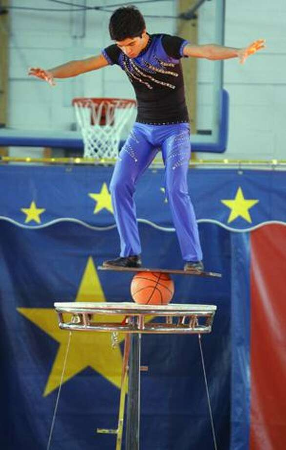 Photo by JOHN HAEGER A circus performer balances atop a basketball during the Billy Martin's Cole All-Star Circus on Saturday, Jan. 29, 2011 at Oneida High School. The circus was sponsored by the Zonta Club of Oneida.
