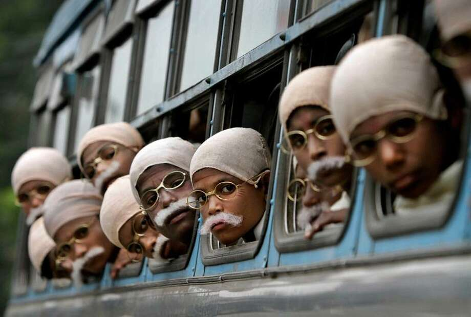 Underprivileged Indian children dressed in costume to look like the late Mahatma Gandhi arrive on a  bus before attempting a world record in Kolkata, India, Sunday. Local non-government organizations put on the event and a total of 485 children took part in the rally ahead of the anniversary of Gandhi's death which falls on January 30th. Associated Press Photo: ASSOCIATED PRESS / AP2012