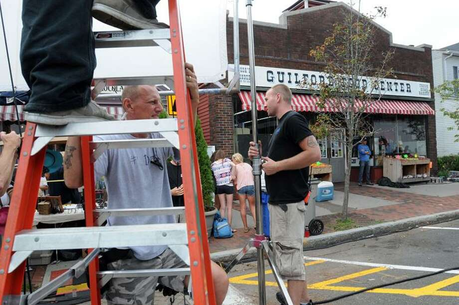 "Lighting technicians for the movie ""Great Hope Springs"" work outside the Guilford Food Center Tuesday. (Mara Lavitt/Register)"