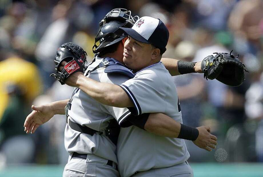New York Yankees' Bartolo Colon, right, and catcher Francisco Cervelli embrace after the 5-0 defeat of the Oakland Athletics at the end of a baseball game Monday, May 30, 2011, in Oakland, Calif. (AP Photo/Ben Margot) Photo: AP / AP
