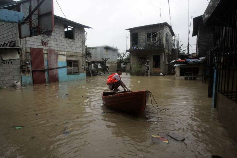 A rescuer sits on his boat as he monitors the rising flood water due to Typhoon Neast, telling people to leave an area in suburban San Mateo, eastern Manila, Philippines, Tuesday. Manila residents waded through waist-deep floodwaters, dodging branches and flying debris as the powerful typhoon sent surging waves as tall as palm trees crashing over seawalls and submerging entire neighborhoods.  Associated Press Photo: AP / AP