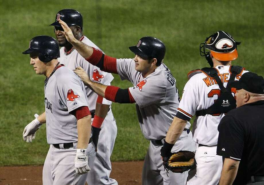The Red Sox's Ryan Lavarnway, left, walks away from home plate with teammates David Ortiz, second from left, and Adrian Gonzalez after Lavarnway drove them  in on a home run in the fourth inning of Tuesday's game against the Baltimore Orioles. The former Yale star added a second homer as Boston won 8-7. (AP photo) Photo: AP / AP2011