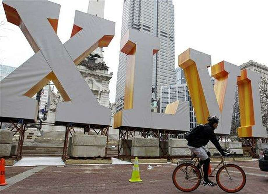 A bicycle messenger pedals past the roman numerals for Super Bowl XLVI at Monument Circle as preparations continue for Super Bowl XLVI NFL football game in downtown Indianapolis, Wednesday, Jan. 25, 2012. The New England Patriots will face the New York Giants on Feb. 5. (AP Photo/Michael Conroy) Photo: ASSOCIATED PRESS / AP2012
