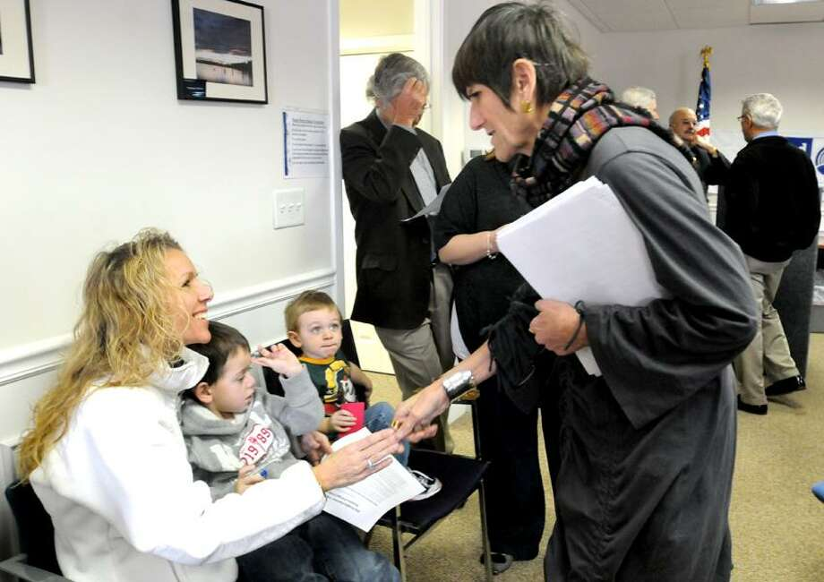 Dawn Murphy, of Bethany, left, meets U.S. Rep. Rosa DeLauro, D-3, at the United Way office where Delauro is speaking on home financing reform. Murphy was there with her sons Jacob, 4, left, and Joshua, 2, to talk about her ordeal with Bank of America.  Melanie Stengel/Register