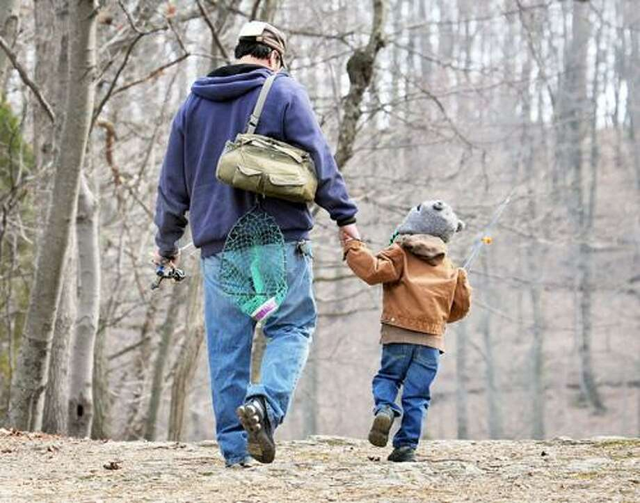 FILE - In this April 3, 2011 file photo, a father and son head for their fishing hole at Muddy Run Recreation Park in southern Lancaster County, Pa. New research suggests that dads are less likely to die of heart-related problems than childless men are. The study by AARP, the government and several universities is the largest ever look at men, fertility and mortality. (AP Photo/Intelligencer Journal, Marty Heisey) Photo: AP / AP2011